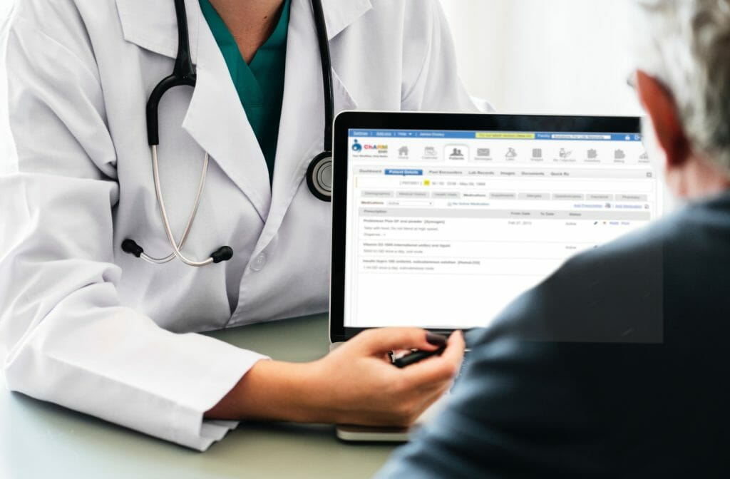 photo showing medical consult with doctor presenting information on laptop